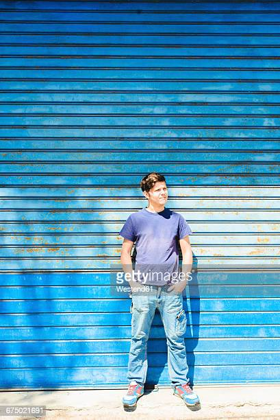 Young man standing in front of blue gate with hands in pockets