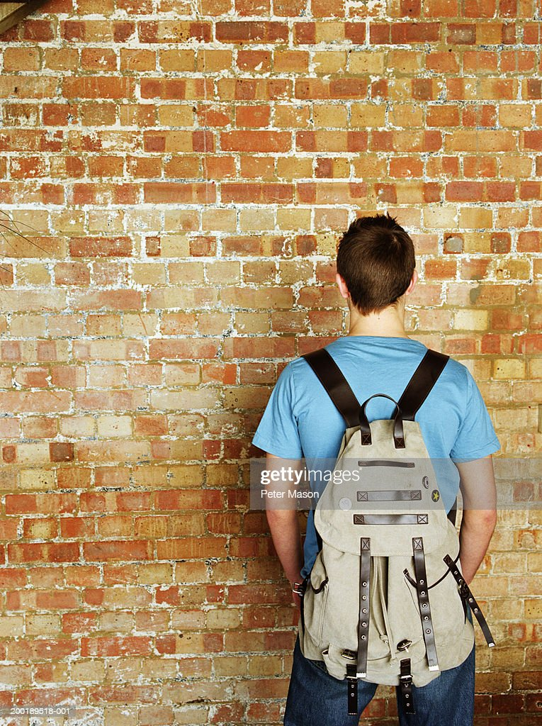 Young man standing in front of brick wall, wearing rucksack, rear view : Stock Photo