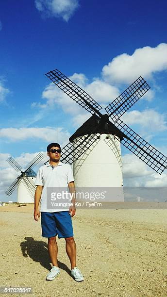 Young Man Standing In Front Of Traditional Windmills