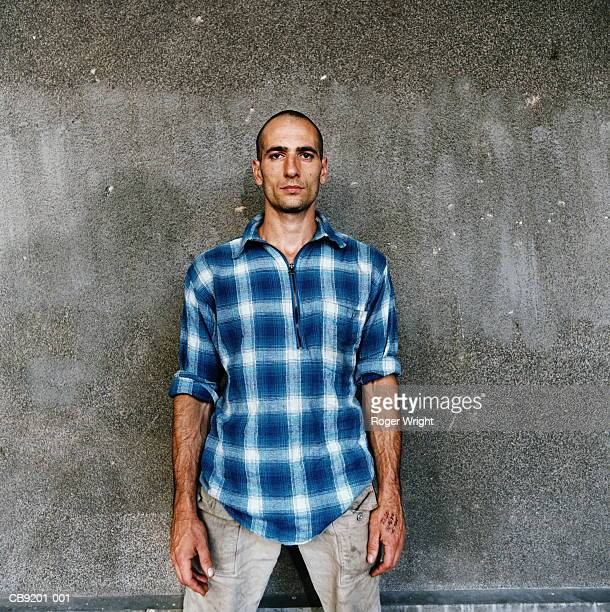 Young man standing in front of wall, portrait