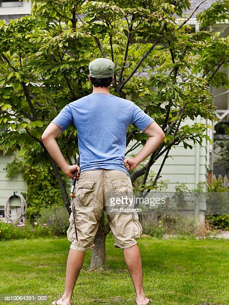 Young man standing in garden with shears, rear view