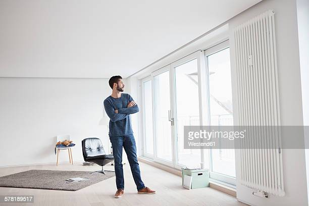 Young man standing in his living room looking through window