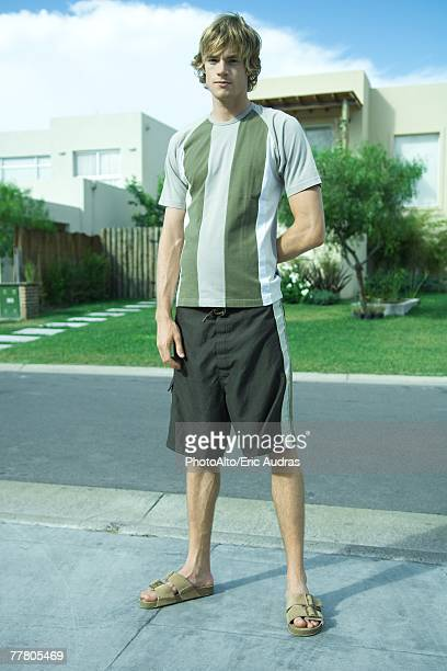 Young man standing in residential neighborhood, full length portrait