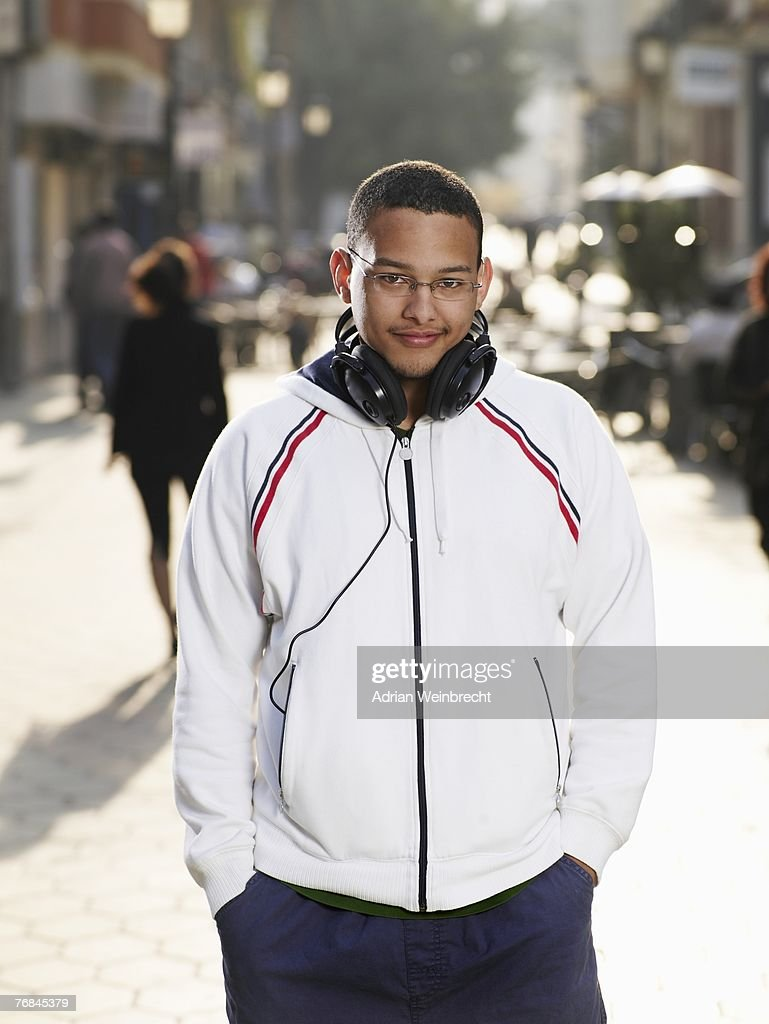 Young man standing in street, smiling, portrait : Stock Photo
