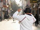 Young man standing in street wearing headphones, rear view