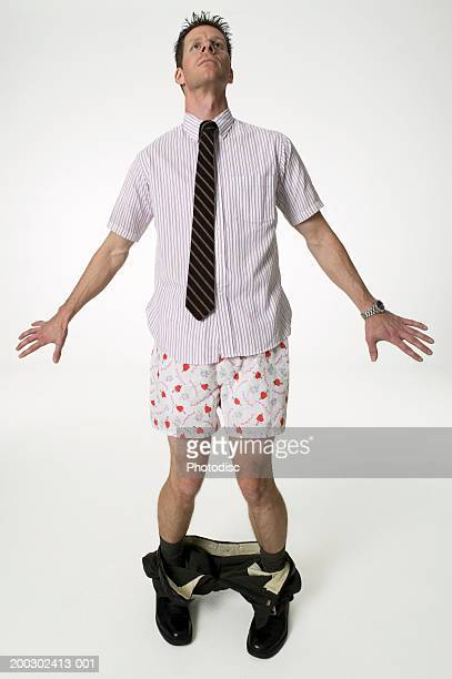 Young man standing in studio with trousers around ankles