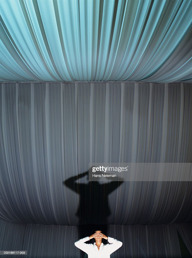 Young man standing in tent, covering eyes : Foto de stock