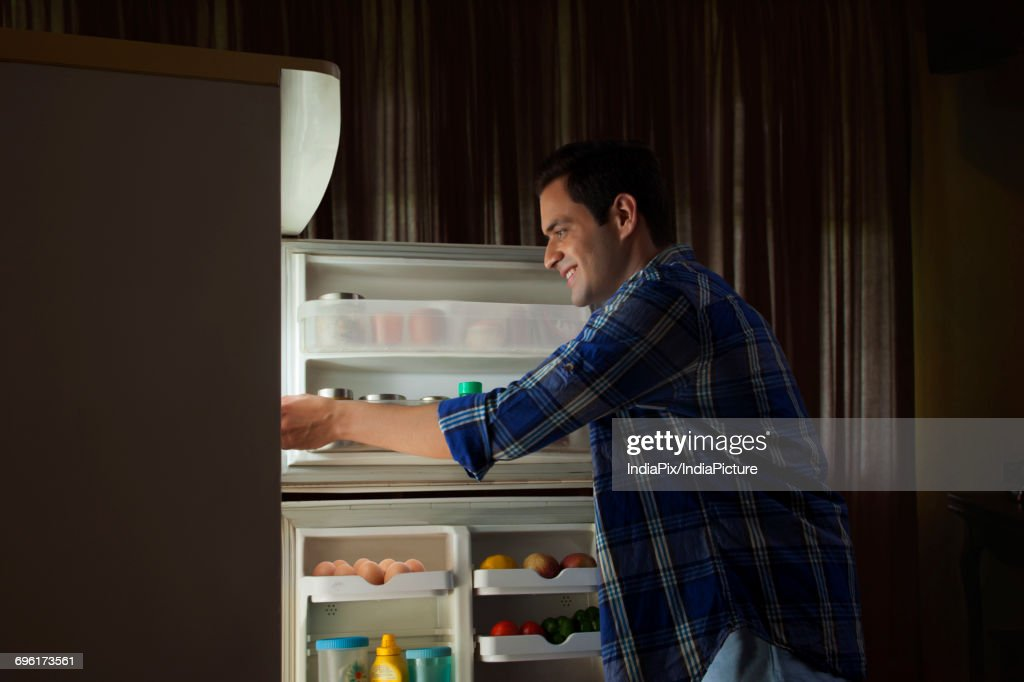 Young Man Standing In The Kitchen Looking In The Fridge Stock ...