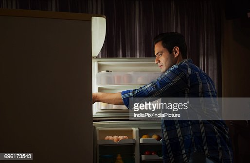 Young Man Standing In The Kitchen Searching Something In The ...