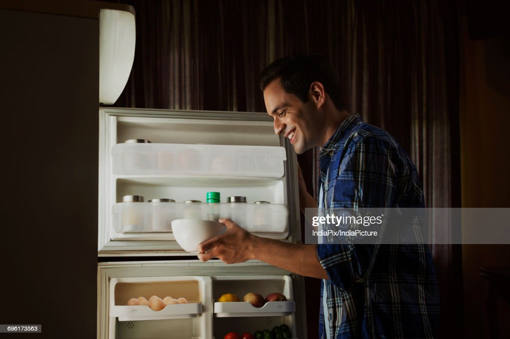 Young Man Standing In The Kitchen Searching Food In The Fridge At ...