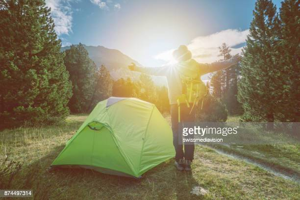 Young man standing near tent arms outstretched, Switzerland