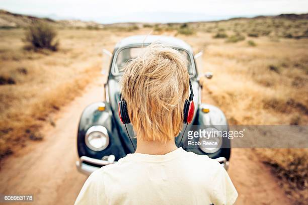 A young man standing next to a 1967 classic Volkswagen Beetle