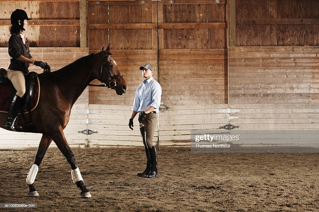Young man standing next to rider and her horse in a training stable : Stock Photo