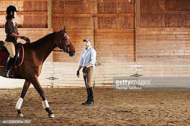 Young man standing next to rider and her horse in a training stable