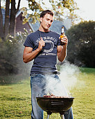 Young Man Standing on a Lawn With a Beer by a Barbecue
