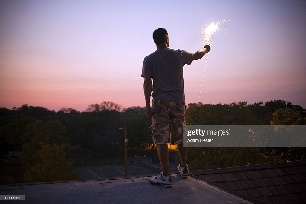A young man standing on a roof with a sparkler.