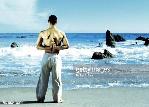 Young man standing on beach, in yoga position, rear view : Stock Photo