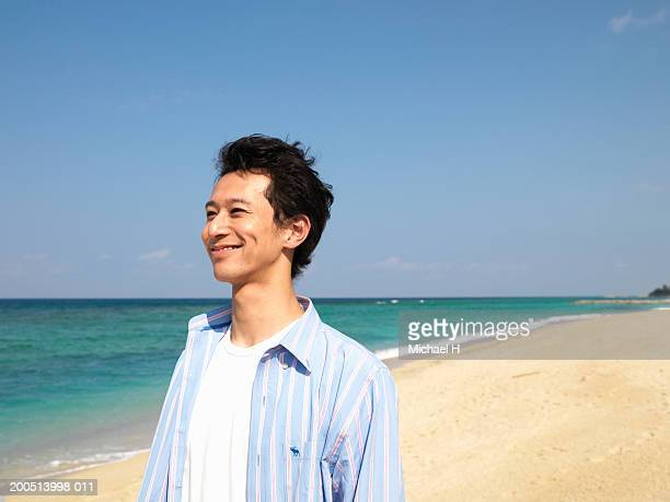 Young man standing on beach, smiling, looking away