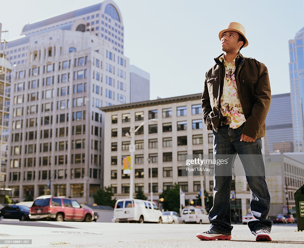 Young man standing on city sidewalk, looking up : Stock Photo