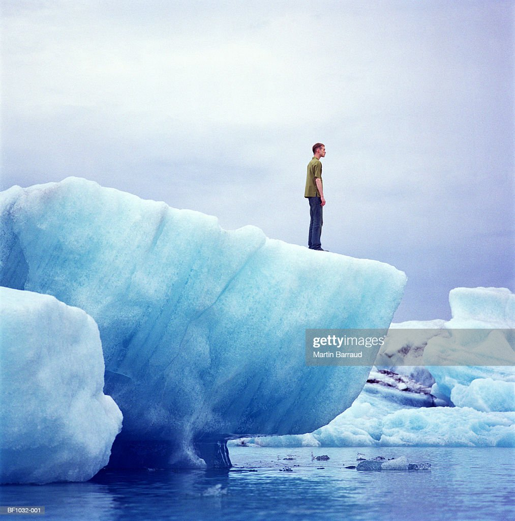 Young man standing on edge of iceberg, profile : Stock Photo
