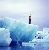 Young man standing on edge of iceberg, profile