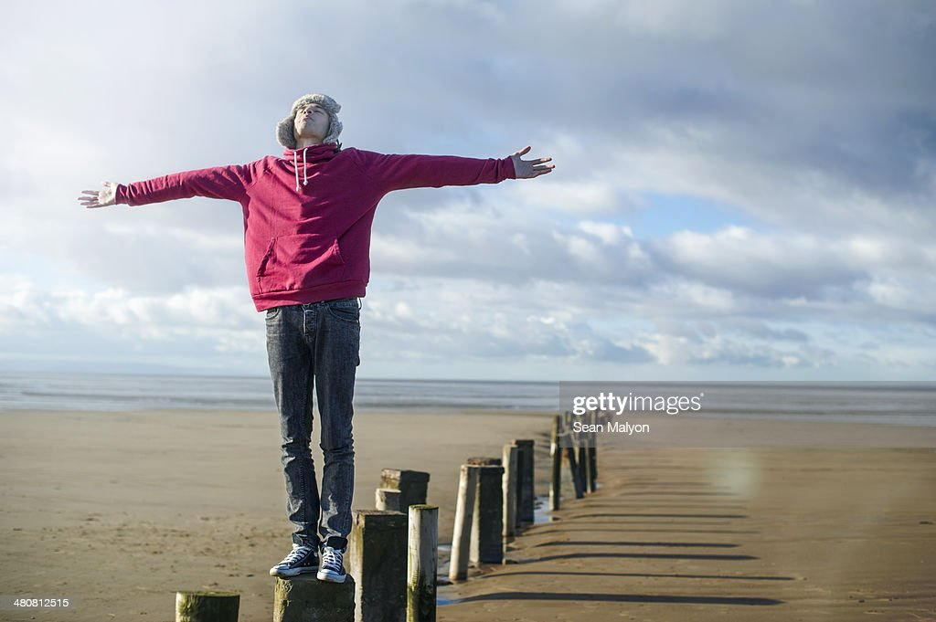 Young man standing on groynes, Brean Sands, Somerset, England : Stock Photo