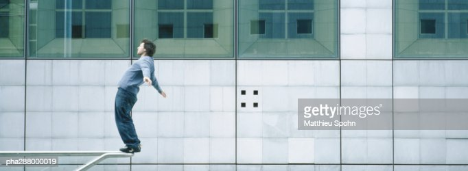 Young man standing on rail