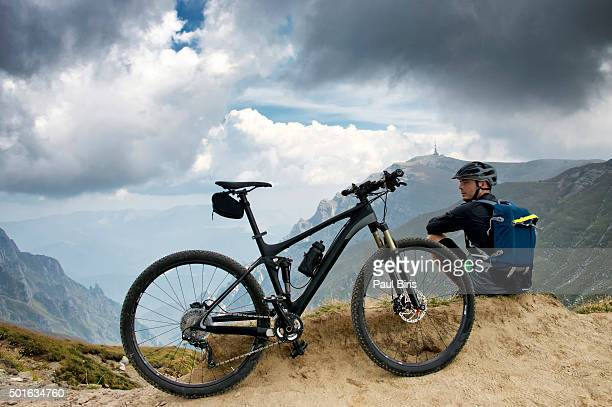 Young man standing on rock formation with mountain bike, Omu peak 2507m