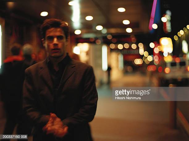 Young man standing on street at night, hands clasped