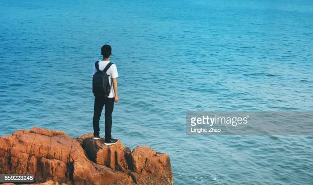 Young man standing on the rock by sea