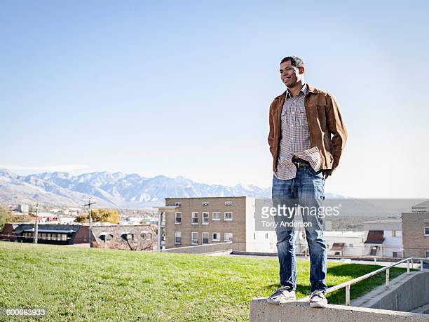 Young man standing on wall city in background