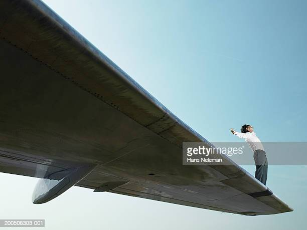 Young man standing on wing of airplane