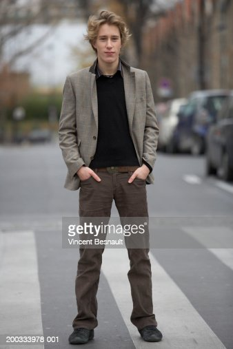 Young man standing on zebra crossing, hands in pockets, portrait : Photo