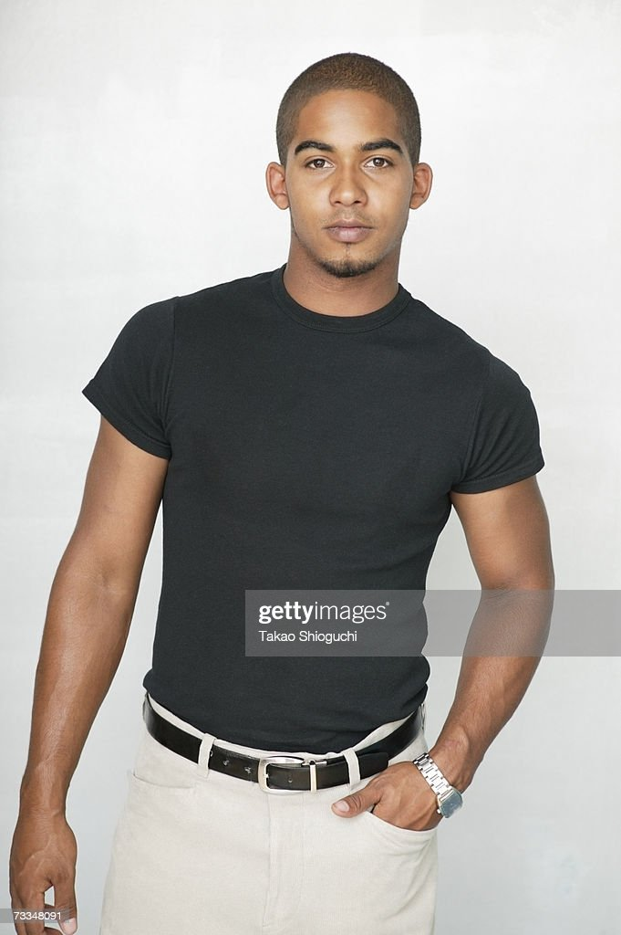 Young man standing, one hand in pocket, portrait