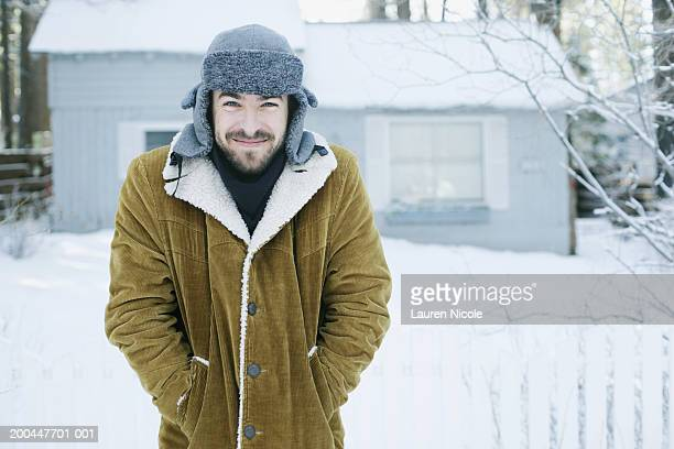 Young man standing outdoors in snow, smiling, portrait