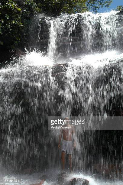 Junger Mann stehend auf rauschende Wasserfälle