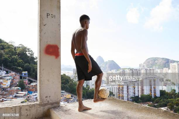 Young man standing with a football balanced on his foot with the city of Rio in the background