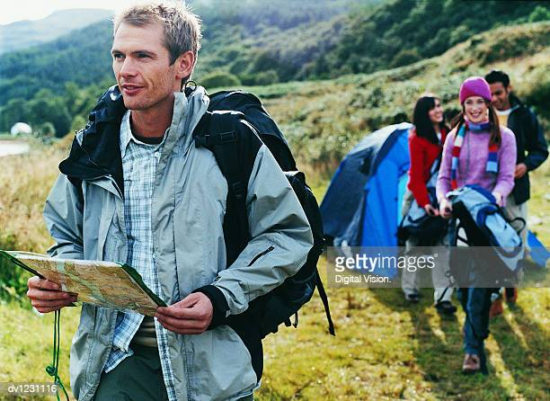 Young Man Standing With a Map in Front of Three People by a Tent Camping in the Countryside