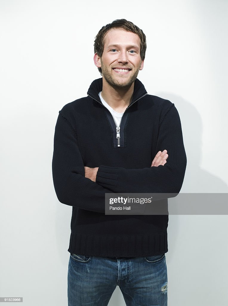 Young man standing with arms crossed, smiling : Stock Photo