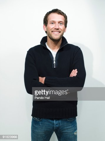 Young man standing with arms crossed, smiling : Stockfoto