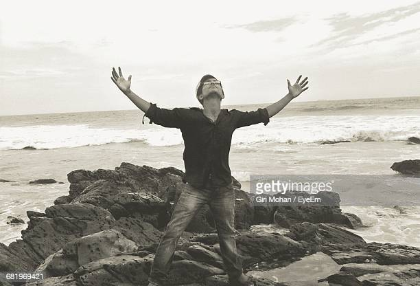 Young Man Standing With Arms Outstretched On Rock Formations At Seashore