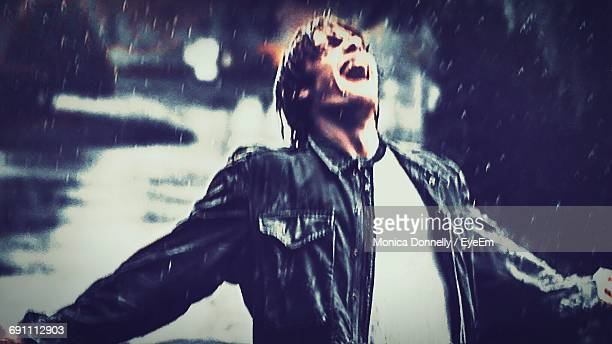 Young Man Standing With Arms Outstretched While Enjoying Rain