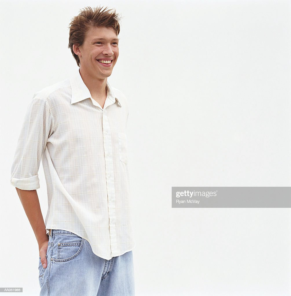 Young man standing with hands in back pockets, smiling, portrait, : Stock Photo