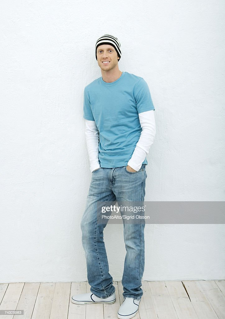 Young man standing with hands in pockets, full length portrait : Stock Photo