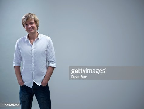 Young man standing with hands in pockets, portrait : Stock Photo