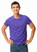 Portrait of happy young man in casual wear standing with hands on hips. Vertical shot. Isolated on white.