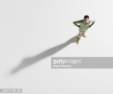 Young man standing with hands on hips, portrait, overhead view : Stock Photo