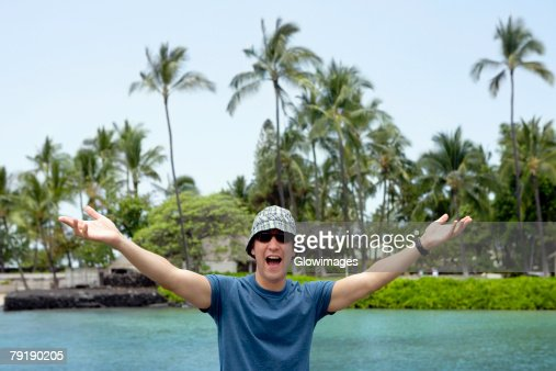 Young man standing with his arms outstretched and shouting, Captain Cook's Monument, Kealakekua Bay, Kona Coast, Big Island, Hawaii islands, USA : Foto de stock
