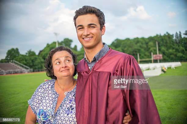 Young man standing with mother at graduation ceremony