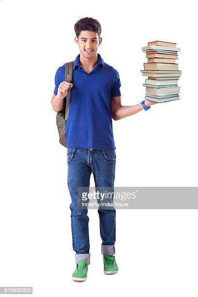 Young Man Standing With Stack of books in hand, isolated on white background
